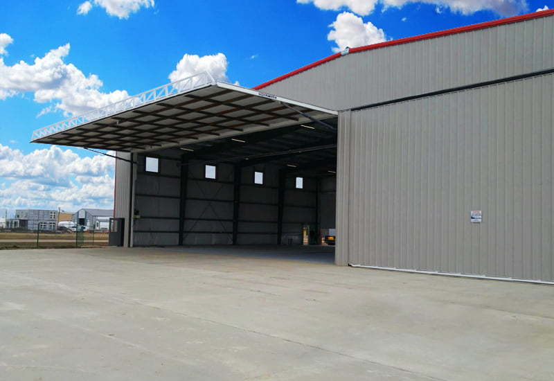 Exterior of a prefab steel airplane hangar with door lifted