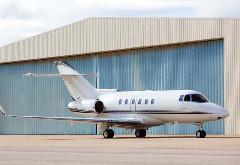 Prefabricated steel airplane hangar with airplane in front and hangar door closed
