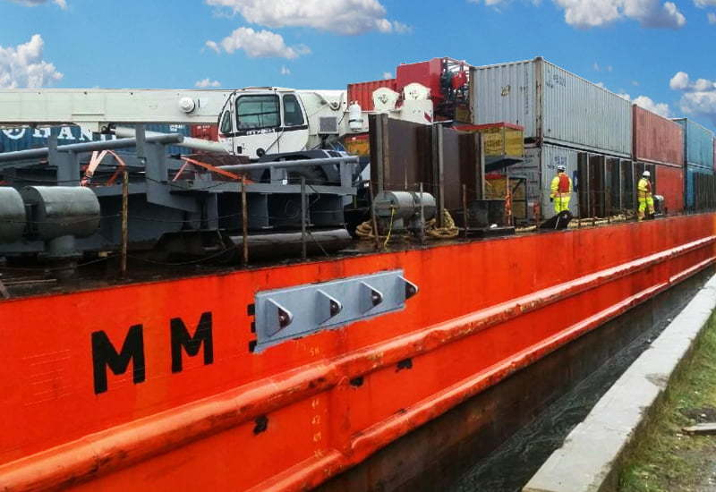 Metal barge carrying 52 containers full of components for a prefab steel mining building