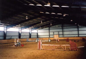 Interior of a prefab steel riding sporting arena with translucent panels and steel rigid frames